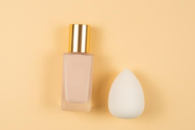 Mały, średni i duży biały beauty blender i podkład do makijażu na beżowym tle. widok z góry.