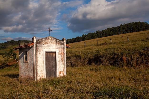 Mały stary biały kościół w wsi w niebieskie niebo dniu
