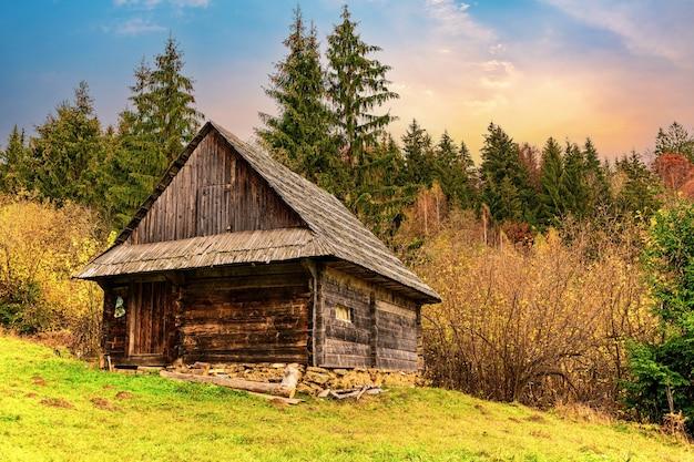 Mały stary dom w małej pięknej dolinie z zielonymi świeżymi łąkami i kolorowymi jesiennymi lasami