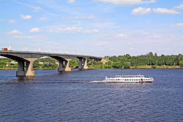 Mały statek motorowy promenady na dużej rzece w pobliżu mostu