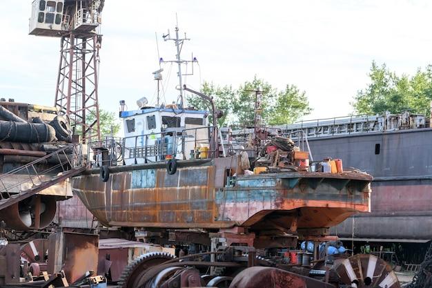 Mały statek na lądzie w stoczni remontowej statków