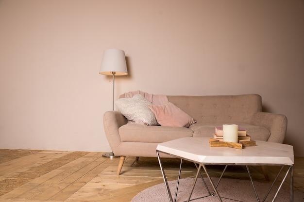Mały stolik kawowy i świece obok zaprojektowanej sofy z pastelowymi poduszkami
