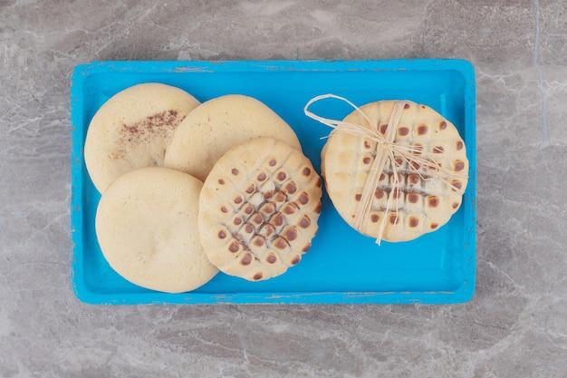 Mały stos ciasteczek na niebieskim talerzu z marmuru