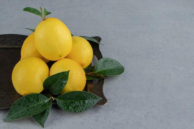 Mały stos cytryn i liści na ozdobnej tacy na marmurze