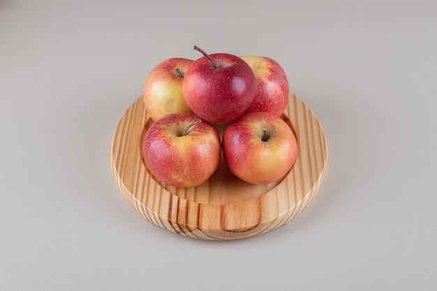 Mały stos jabłek na drewnianym talerzu z marmuru