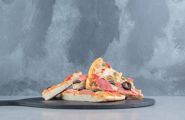 Mały stos plasterków pizzy na czarnej tablicy na marmurze