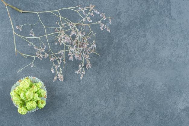 Mały stos zielonych cukierków popcornowych obok ozdobnych gałęzi na marmurze