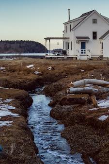 Mały strumień przepływający przez ziemię przez duży biały dom z lasem w tle