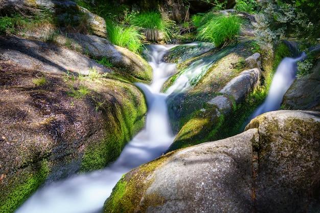 Mały strumień w górach między skałami