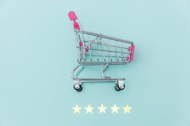 Mały supermarket wózek sklepowy na zakupy zabawki na kółkach i 5 gwiazdek na białym tle na pastelowym niebieskim tle. konsument detaliczny kupujący online ocenę i przegląd koncepcji.