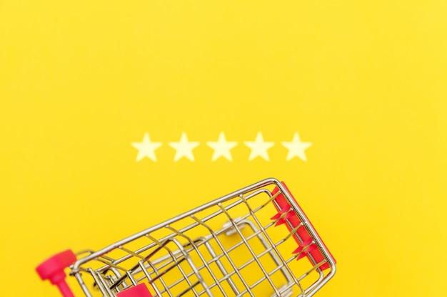 Mały supermarket wózek sklepowy na zakupy zabawki na kółkach i 5 gwiazdek na białym tle na żółtym tle. konsument detaliczny kupujący koncepcję oceny i przeglądu online.