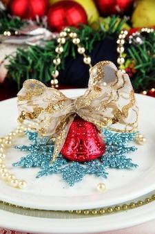 Mały świąteczny dzwonek na talerzu na serwowaniu świątecznego stołu zbliżenie tła