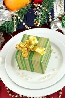 Mały świąteczny prezent na talerzu na serwowaniu świątecznego stołu zbliżenie tła