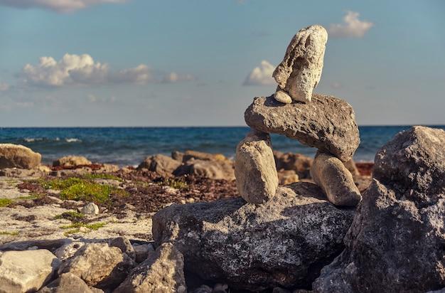 Mały symboliczny budynek z naturalnymi skałami na plaży puerto aventuras w meksyku