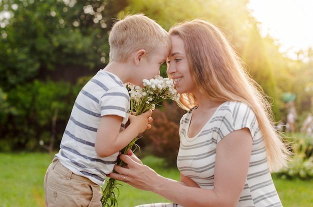 Mały syn daje matce bukiet delikatnych kwiatów.