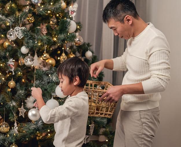 Mały syn i ojciec dekorują choinkę na święta w domu