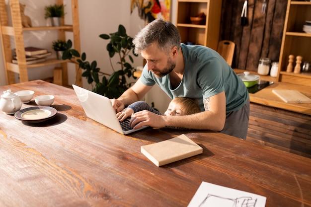 Mały syn próbuje pisać na ojca laptopie
