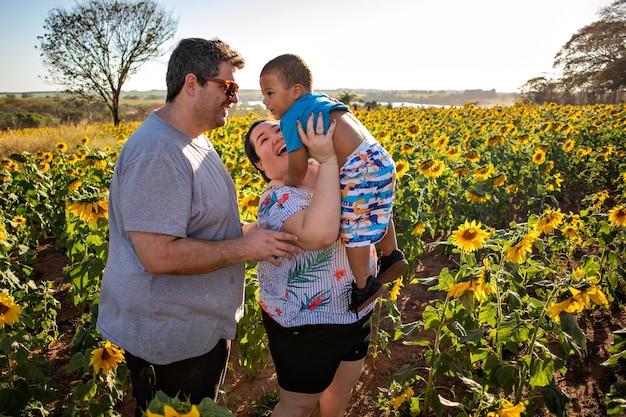 Mały synek w towarzystwie szczęśliwych młodych przybranych rodziców i bawiący się na słonecznikowym polu.