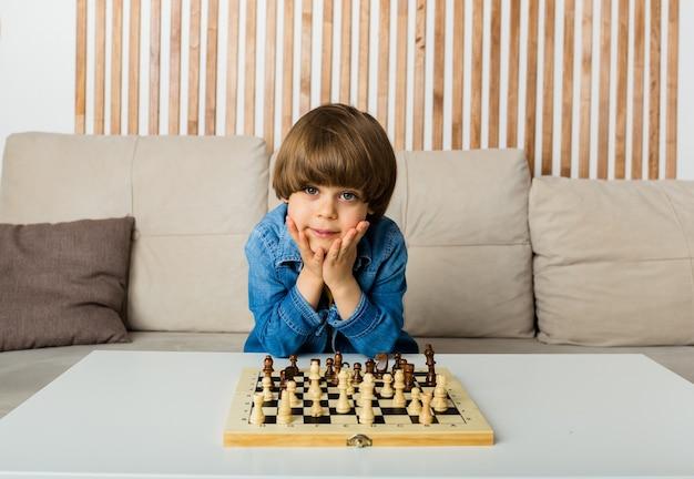 Mały szachista w dżinsowej koszuli gra w szachy i patrzy w kamerę
