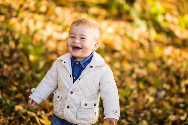Mały szczęśliwy chłopiec z uśmiechem bawi się liśćmi w złotym jesiennym parku.