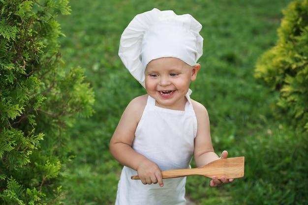 Mały szczęśliwy szef kuchni na pinkinie outdoors