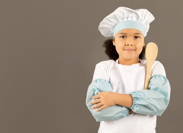 Mały szef kuchni pozuje z drewnianą łyżką