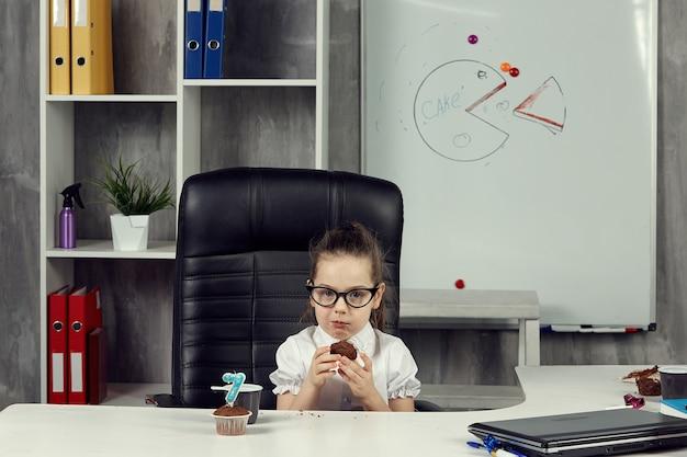 Mały szef zjada ciastko pomiędzy pracą.