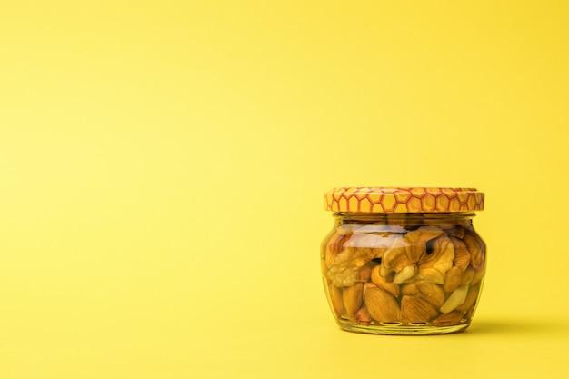 Mały szklany słoik z miodem i orzechami na żółtym tle.