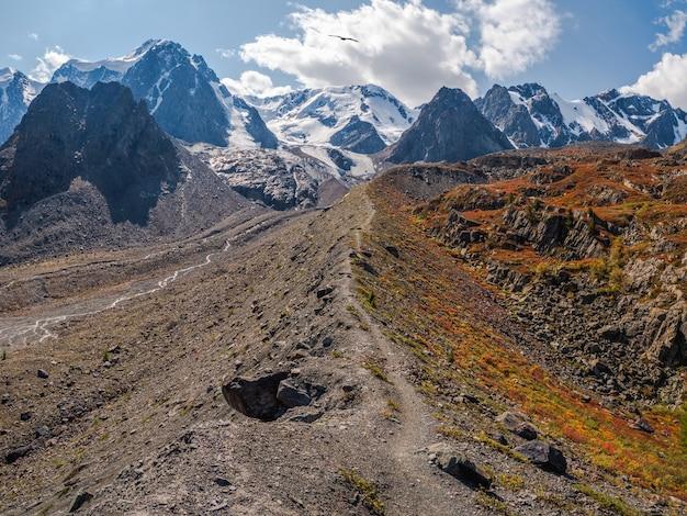 Mały szlak turystyczny wzdłuż grzbietu górskiego. kolorowy słoneczny krajobraz z klifem i dużymi górami skalistymi oraz epickim głębokim wąwozem. góry ałtaj.