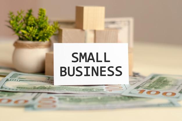 Mały tekst biznesowy na białym papierze, na rachunkach pieniężnych, banknotach i drewnianych klockach, koncepcja biznesowa