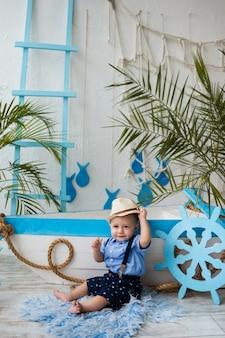 Mały Turysta W Słomkowym Kapeluszu Siedzi Obok Drewnianej łodzi Na Powierzchni Z Morskimi Dekoracjami Premium Zdjęcia