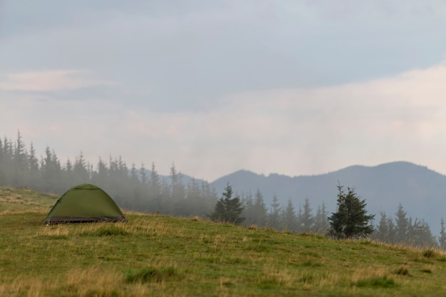 Mały turystyczny namiot na trawiastym górskim wzgórzu. letni camping w górach o świcie.
