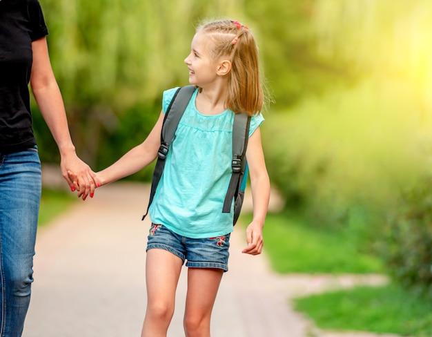Mały uczeń idący ramię w ramię z matką w słonecznym parku