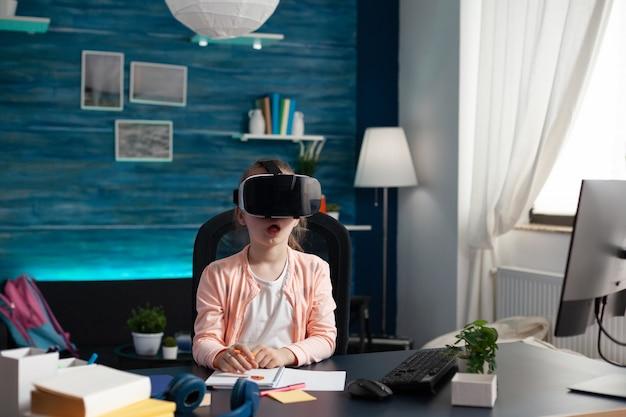 Mały uczeń na biurku w domu używa okularów vr na zajęciach