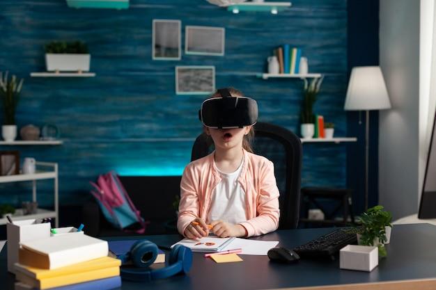Mały uczeń noszący zestaw wirtualnej rzeczywistości, który bawi się w okularach vr