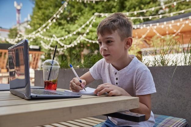 Mały uczeń odrabia lekcje na zewnątrz z laptopem pisząc notatki w zeszycie