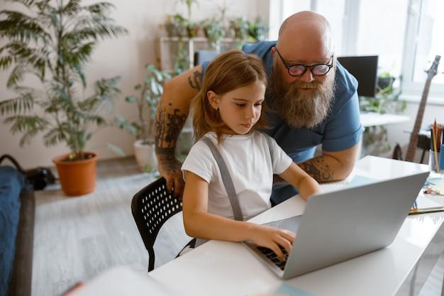 Mały uczeń pracuje na laptopie, podczas gdy tata stoi obok w domu