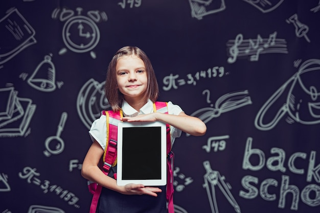 Mały uczeń przygotowuje się do pójścia do szkoły z plecakiem pokazującym tablet z powrotem do koncepcji szkoły