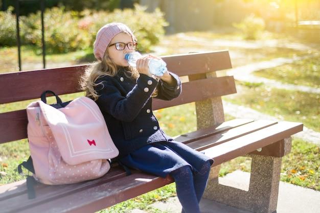 Mały uczeń siedzi na ławce z plecakiem, woda pitna z butelki