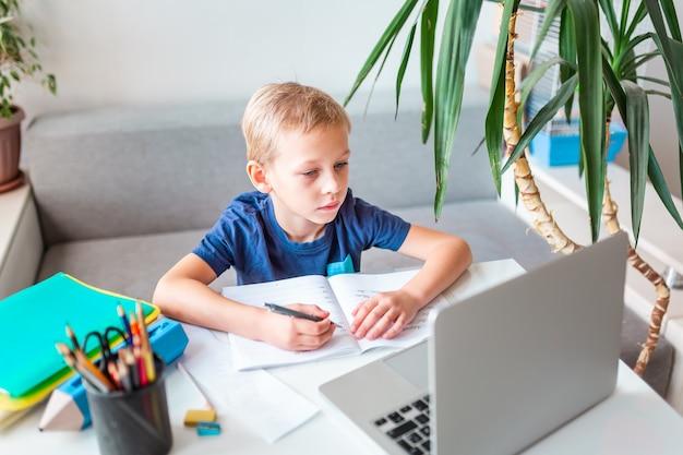 Mały uczeń uczy się w domu z laptopem