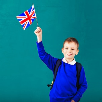 Mały uczeń z flagą narodową wielkiej brytanii. koncepcja szkoły. powrót do szkoły