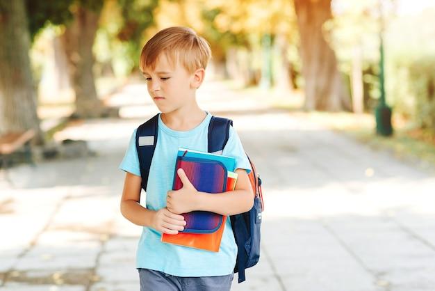 Mały uczeń z negatywnymi emocjami idzie do szkoły. edukacja, powrót do koncepcji szkoły. nieszczęśliwy chłopiec szkoły z książkami w ręce i plecak na ulicy.