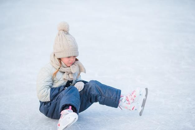 Mały uroczy dziewczyny obsiadanie na lodzie z łyżwami po spadku
