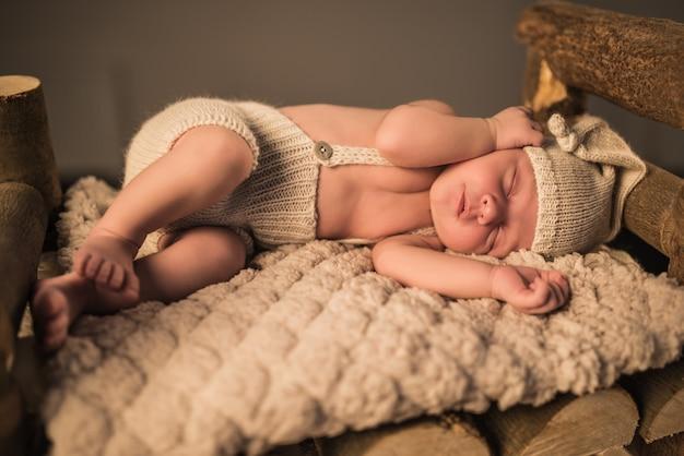 Mały uroczy noworodek w dzianinowym garniturze i czapce śpi na miękkiej wełnianej kracie