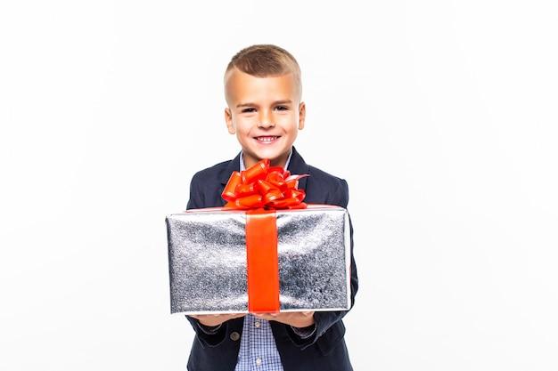 Mały uśmiechnięty chłopiec mienia teraźniejszości pudełko odizolowywający na biel ścianie