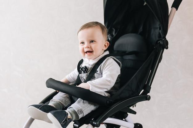 Mały uśmiechnięty chłopiec siedzi w wózku dziecięcym