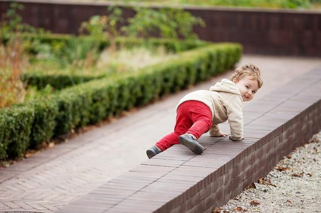 Mały uśmiechnięty chłopiec skrada się w parku