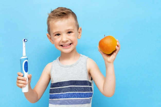 Mały uśmiechnięty chłopiec z elektryczną szczoteczką do zębów i jabłkiem w rękach na niebiesko