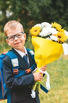 Mały uśmiechnięty chłopiec z kwiatami gotowy do wyjścia w pierwszej klasie w szkole uczeń w szkolnym mundurku