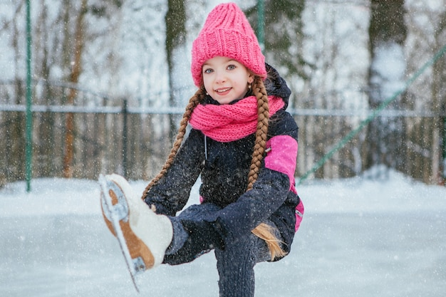 Mały uśmiechnięty dziewczyny łyżwiarstwo na lodzie w menchiach jest ubranym. zimowy